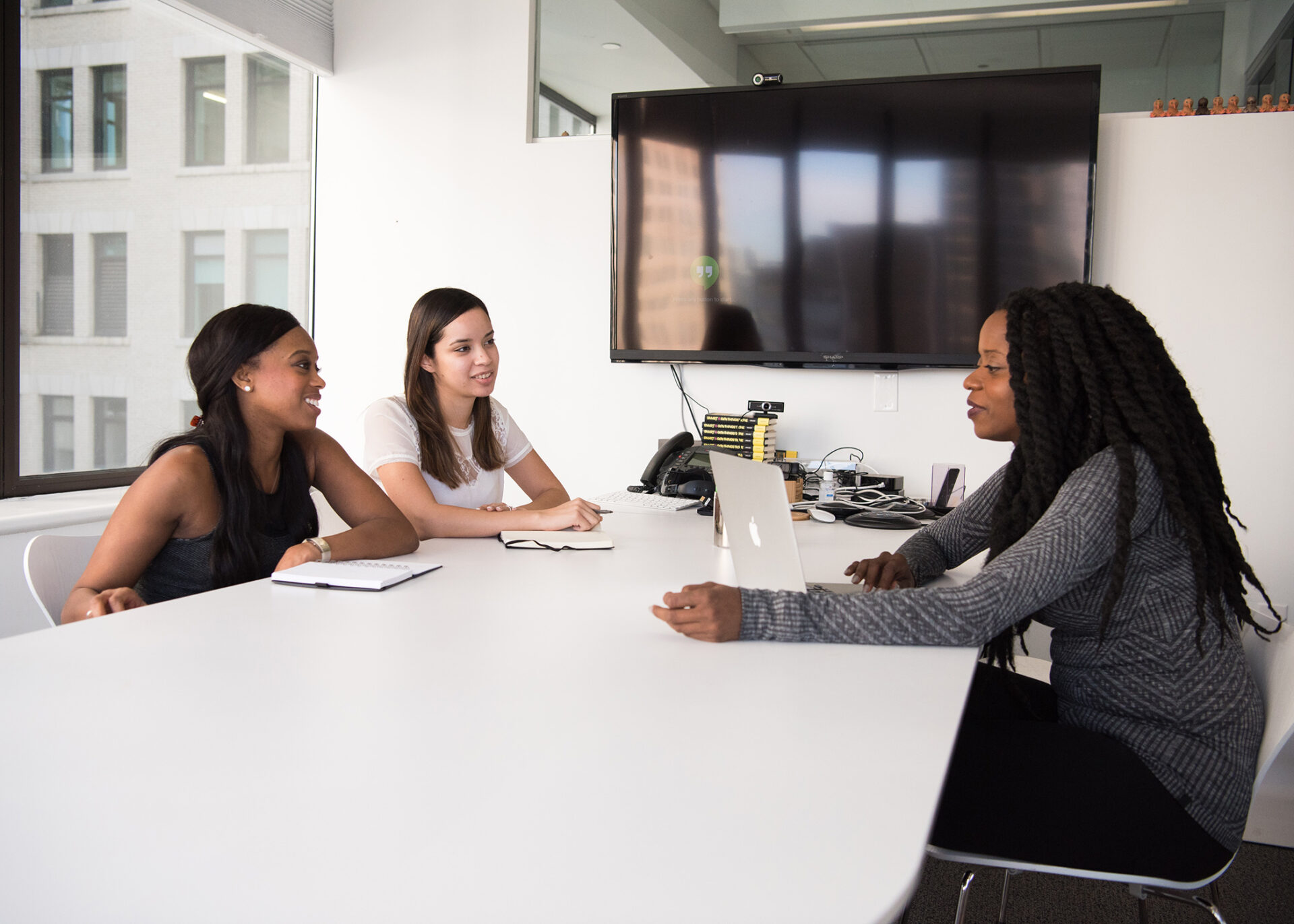 Three Women Sit in a Business Meeting